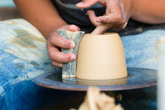 Potter creating clay bowl on turning wheel Royalty Free Stock Photo