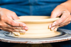 Potter creating clay bowl on turning wheel Stock Photography