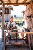 Potter is creating earthenware on potter`s wheel. stock photos