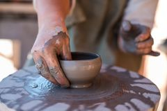 Potter is creating earthenware on potter`s wheel. royalty free stock images