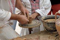 Potter guiding pottery to boy. Potter teaching young person making pot on wheel Stock Images