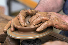 Potter hands clay bowl. Potter shaping a bowl on a pottery wheel Stock Photography