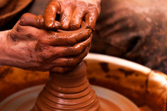Potter hands pot. Potter hands working with clay making a pot which is placed on potter`s wheel Stock Photo