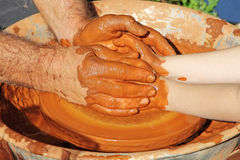 Potter hands wheel pottery work workshop teacher and little pupil Stock Image