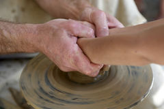 Potter helping person. Potter helping a person making a pottery Stock Image