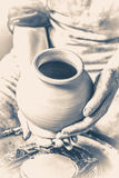 Potter holds more crude to the firing of white clay jug. Old vintage style. Stock Images