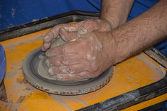 Potter makes on the pottery wheel clay jug. The hands of a potte. Production of ceramic vessel on the potter's wheel Royalty Free Stock Images