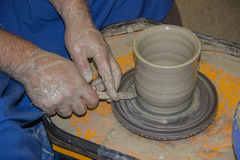 Potter makes on the pottery wheel clay jug. The hands of a potte. Production of ceramic vessel on the potter's wheel Royalty Free Stock Photos