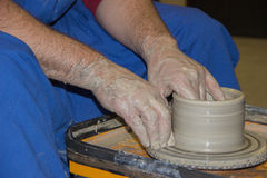 Potter makes on the pottery wheel clay jug. Production of ceramic vessel on the potter's wheel Royalty Free Stock Photo