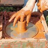 Potter makes on pottery wheel clay pot. Royalty Free Stock Photo
