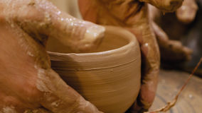 Potter is making clay pot on the potter`s wheel. Potter is making clay pot bowl or vase ceramics porcelain on the potter`s wheel. Creating pottery art and Stock Photography