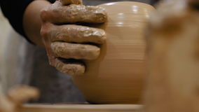 Potter is making clay pot on the potter`s wheel stock video