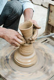 A Potter making clay pots. An artisian making clay pots on pottery wheel Royalty Free Stock Images