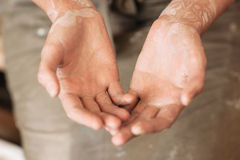 Potter messy palms in clay, working hands Stock Photos