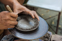 Potter is molding and craving the clay. Royalty Free Stock Image