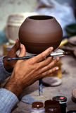 Potter- Peru. Potter beginning to apply the slip (paint) onto clay pot in workshop in the Incan village of Ollantaytambo (Sacred Valley), Peru Stock Image