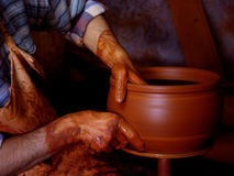 The potter's hands. A potter working on a lathe to create a pot stock image