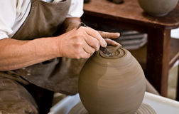The potter's hands. Close shot of a potter molding a vase in the turning wheel Royalty Free Stock Image