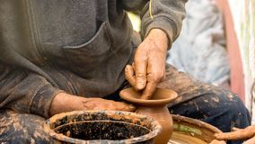Potter`s hands creating a clay vase on a circle. royalty free stock photo