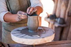 Potter is creating earthenware on potter`s wheel. stock images