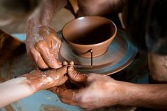 Potter`s hands guiding child`s hands to help him to work with the pottery wheel stock photo