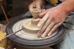 Potter's hands shaping candlestick. Close-up view of potter's hands shaping a clay candlestick on a spinning wheel in an Asian pottery stock images