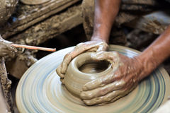 Potter's wheel and hands of craftsman hold a jug Stock Photo
