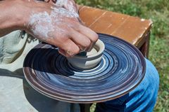 On the potter`s wheel revolve a spinning of a clay cup royalty free stock photos