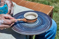 On the potter`s wheel revolve a spinning of a clay cup. Potter puts a paint on the cup Stock Photography