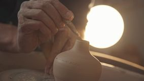 Potter`s wheel, top view, toned cinematic, craft factory authentic. Close up of hands working clay on potter`s wheel. Potter shapes the clay product with pottery stock video footage