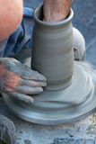 Potter's wheel turning. Closeup on the hands of a potter with his wheel molding a vertical vase of gray clay Stock Photos