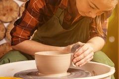 Potter sculpts a deep bowl stock photography