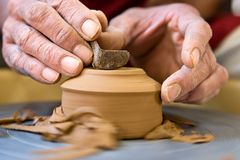 Potter shaping the bottom of a cup on a spinning. Potter's hands shaping the bottom of a cup on a spinning wheel stock photos