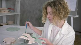 Potter skill, portrait of young inspiring artisan woman working with newly finished pottery plate and drawing via brush stock footage