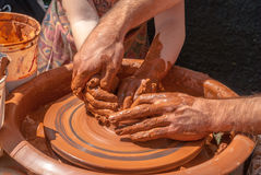 Potter teaches to sculpt in clay pot on a turning pottery wheel Stock Image