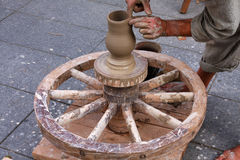 Potter using traditional wheel. Arms of potter making clay vase on traditional wooden wheel Royalty Free Stock Photography