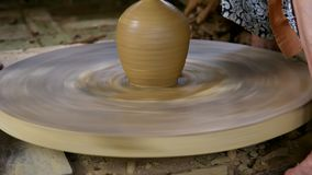 Potter wheel rotates fast and women take off clay pot stock footage