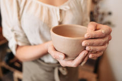 Potter woman keeping clay bowl in dirty palms. Closeup. Unrecognizable female craftsman with her creation at studio Stock Photos