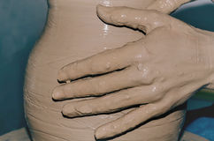 Potter working clay. Pottery making, close up of potter's hands shaping a bowl on the spinning by clay Stock Image