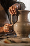 Potter working a piece of clay. Makes a jug Stock Photography
