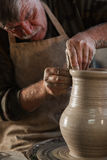 Potter working a piece of clay. Makes a jug Stock Image