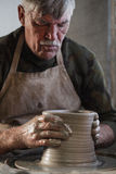 Potter working a piece of clay. Makes a jug Royalty Free Stock Photos