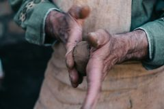 Potter works with clay, craftsman hands close up, kneads and moistens clay. Potter works with clay, craftsman hands in blurred motion, close up, kneads and Royalty Free Stock Photos