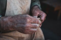 Potter works with clay, craftsman hands close up, kneads and moistens clay. Toned Stock Image