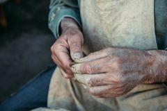 Potter works with clay, craftsman hands close up, kneads and moistens clay. Toned Stock Images