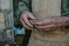 Potter works with clay, craftsman hands close up, kneads and moistens clay. Toned Royalty Free Stock Images