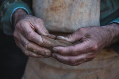 Potter works with clay, craftsman hands close up, kneads and moistens clay. Toned Royalty Free Stock Photos