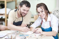 Pottering Ideas. Two Happy Caucasian Ceramists Painting and Glazing. Clay Crafts Together in Workshop Using Paintbrushes. Woman Looking at camera. Horizontal Stock Image
