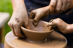 Potters and child hands. A potters hands guiding a child hands to help him to work with the ceramic wheel Stock Photography