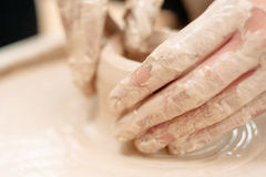 Potters dirty hands on potter wheel close-up Stock Image